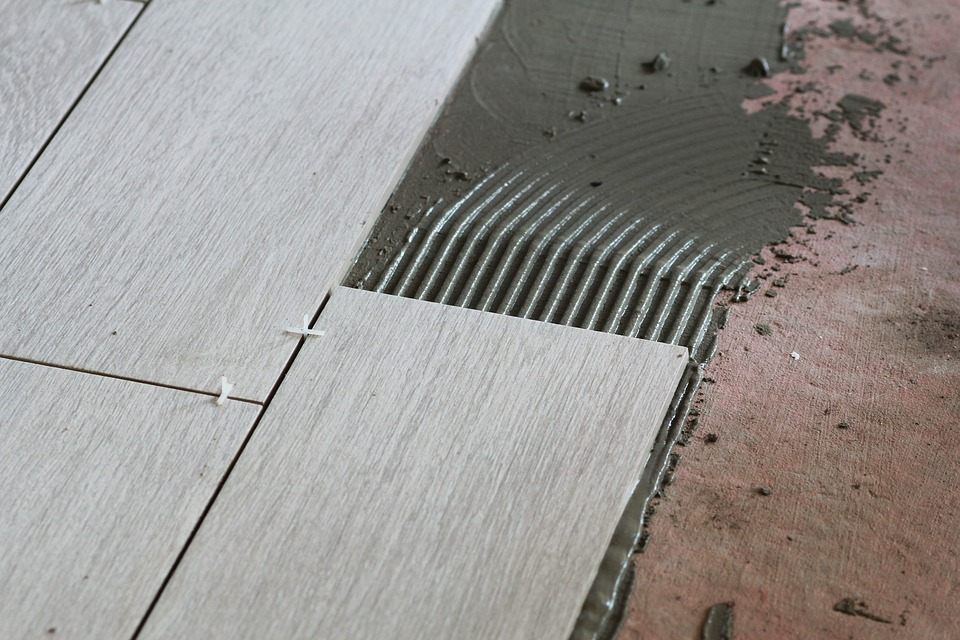 Encollage de carreaux gris avec colle-ciment