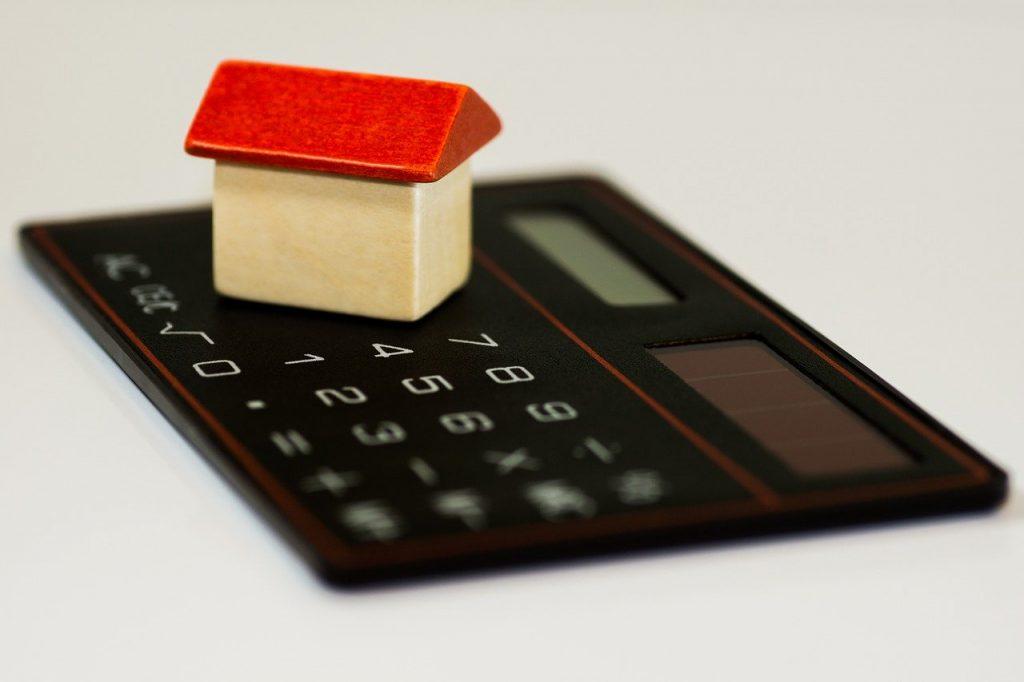 calculatrice sur laquelle est posée une maison miniature